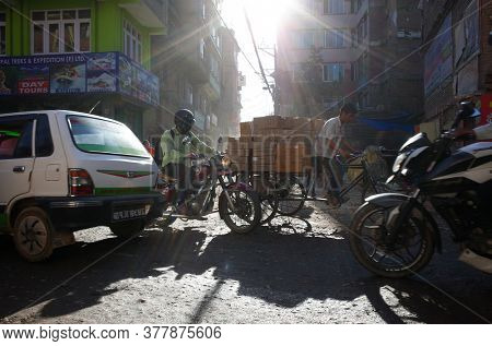 Kathmandu, Nepal - June 20, 2019: Crazy traffic on narrow street in old town with opposite sun and long shade, Local daily life