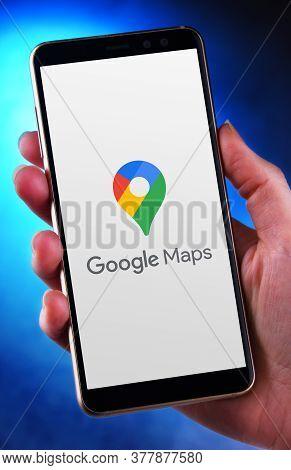 Hand Holding Smartphone Displaying Logo Of Google Maps