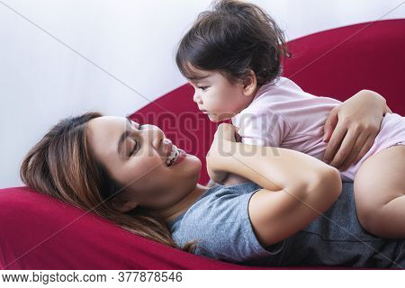Playful Young Mother And Mixed Race Daughter Having Fun While Lying Down Together On Red Sofa In Liv