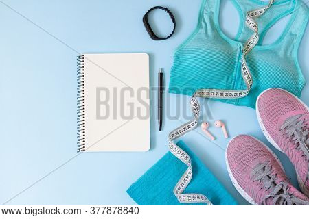 Workout Plan Concept. Stylish Women's Sport Equipments, Wear, Gadgets And Blank Notepad Top View