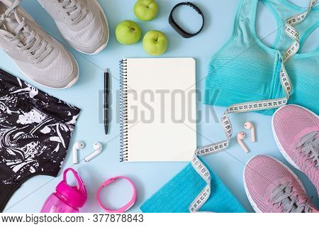 Gym Wear And Accessories For Women With Blank Notebook For Exercise Plan On Blue Background