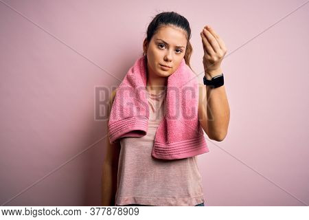 Young beautiful brunette sportswoman wearing sportswear and towel over pink background Doing Italian gesture with hand and fingers confident expression