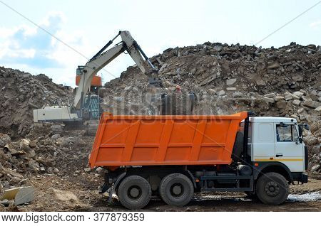 Excavator Loads Construction Waste Into Reinforced Concrete Mobile Shredder For Crushing, Recycling