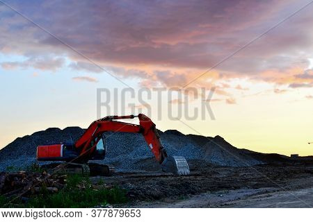 Large Tracked Excavator On A Construction Site Against The Background Of The Awesome Sunset. Road Re