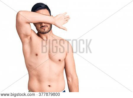 Young handsome man wearing swimwear covering eyes with arm, looking serious and sad. sightless, hiding and rejection concept