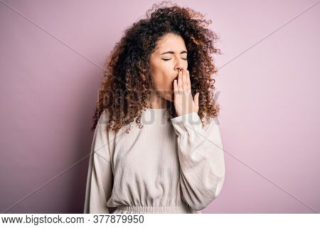 Beautiful woman with curly hair and piercing wearing casual sweater over pink background bored yawning tired covering mouth with hand. Restless and sleepiness.