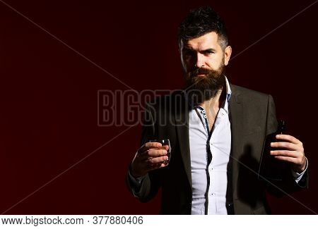 Sommelier With Beard Tasting Alcohol. Man Holding Glass Of Bourbon