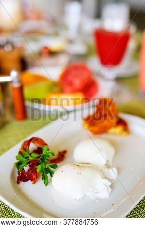 Poached eggs served for breakfast with vegetables, watermelon juice and fruits