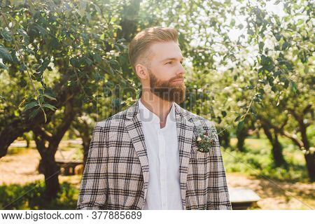 Portrait Of Caucasian Stylish Bearded Groom In Vintage Suit Posing Outdoors In Sunny Weather. Handso