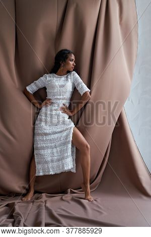 Full Length View Of Pretty Girl With Black Curly Hair Posing Among Brown Fabric, Hands On Waist. Stu