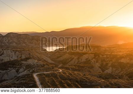 Road Leading Into The Chalk Stone Hills Of Murcia Spain With Orange Sunset.