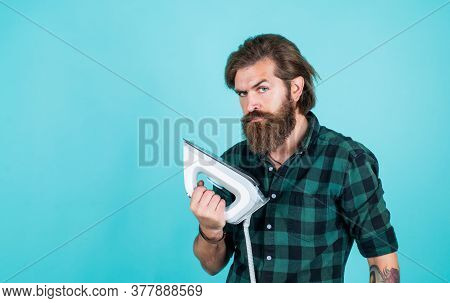 How To Use It. Man Concentrated On Ironing A Shirt. Laundry Room At Home. Clothes Ironing Board Hous