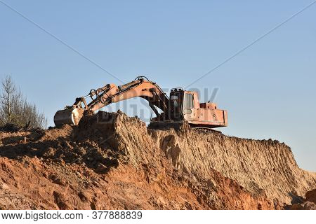 Excavator During Earthmoving At Open Pit On Blue Sky Background. Construction Machinery And Earth-mo