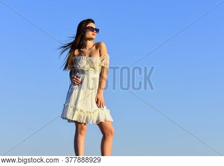 She Got Great Style. Happy Young Woman Posing Over Blue Sky. Pretty Young Beautiful Woman In Sunglas