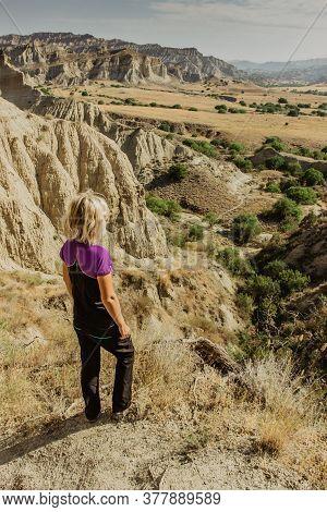Girl Enjoying The View Of Semi Dessert Area.happy Young Active Backpacker Climbing In Vashlovani Par