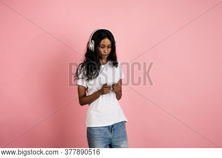 Listen To Music, Watching Video. Cheerful African-american Young Woman On Pink Background, Emotional