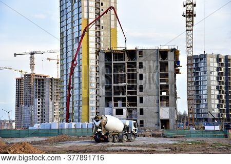 Heavy Mixer Concrete Truck For To Be Loaded Concrete At A Construction Site. Tower Crane Lifting A C