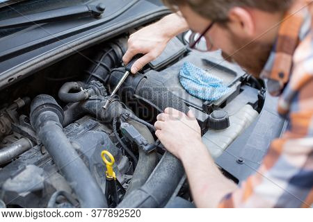 Horizontal View Of A Man Fixing A Car With A Screwdriver. Self Automobile Repair.
