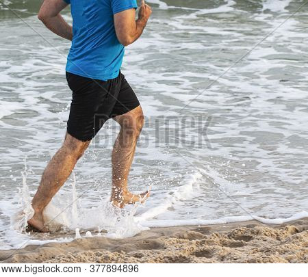 Side View Of A Man Is Running In The Ocean On The Waters Edge Barfoot.