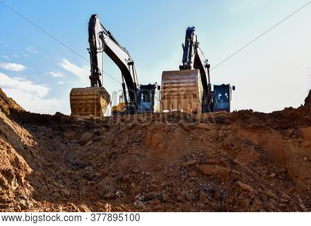 Excavators During Earthmoving At Open Pit On Blue Sky Background. Construction Machinery And Earth-m