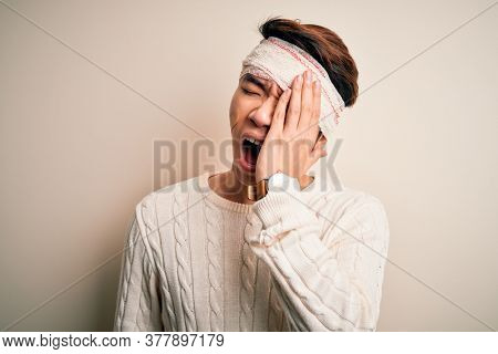 Young handsome chinese man injured for accident wearing bandage and strips on head Yawning tired covering half face, eye and mouth with hand. Face hurts in pain.