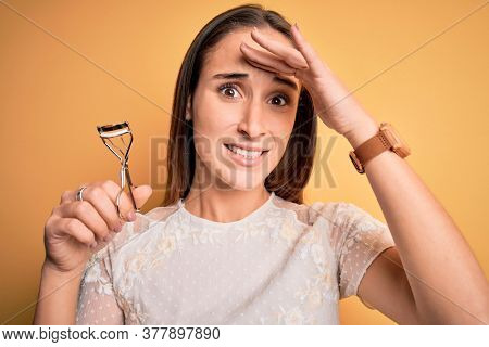 Young beautiful woman using eyelash curler standing over isolated yellow background stressed with hand on head, shocked with shame and surprise face, angry and frustrated. Fear and upset for mistake.