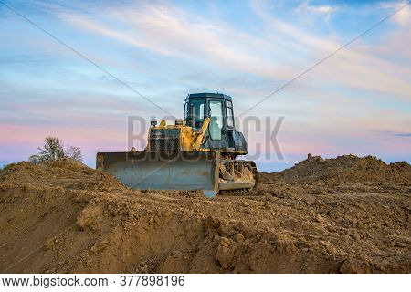 Dozer At Open Pit Mining On Sunseet Background. Bulldozer For Land Clearing, Grading, Pool Excavatio