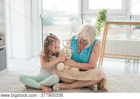 Cute little girl playing plush teddy bear toy with mature woman sitting on floor in modern apartment