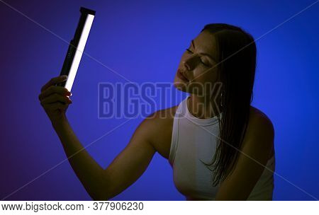 Young Woman Holds Led Lamp Posing On Blue Background. Female Model At Presentation Of Nanlite Studio