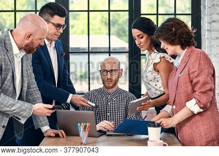 Too Many Work. Selective Focus Of Young Business Man Surrounded By Colleagues, Each Proposes A Proje