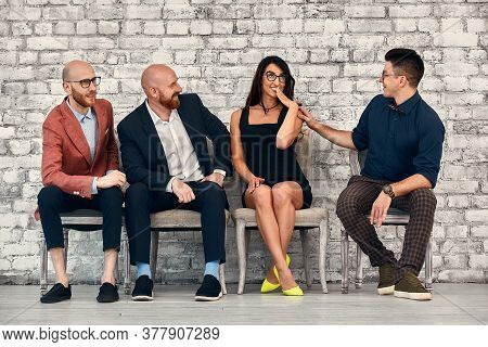 Beautiful Cheerful Professional Woman Wearing Eyeglasses Seated With Male Co-workers And Team Leader