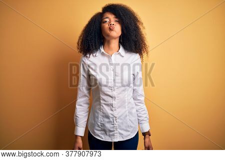 Young beautiful african american elegant woman with afro hair standing over yellow background puffing cheeks with funny face. Mouth inflated with air, crazy expression.