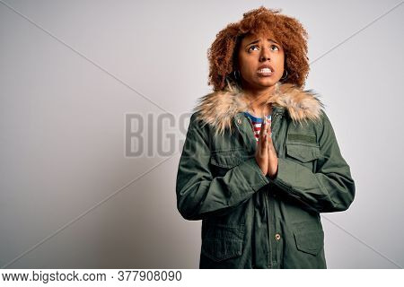 Young beautiful African American woman with curly hair wearing green casual winter coat begging and praying with hands together with hope expression on face very emotional and worried. Begging.