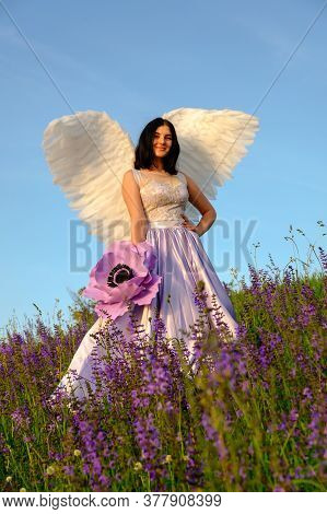 Girl With Angel Wings Stands On A Hillside And Holds A Large Violet Flower