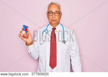 Middle age senior grey-haired cardiologist doctor man holding professional medicine heart with a confident expression on smart face thinking serious