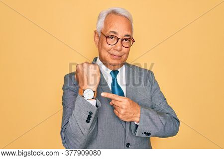 Middle age senior grey-haired handsome business man wearing glasses over yellow background In hurry pointing to watch time, impatience, looking at the camera with relaxed expression