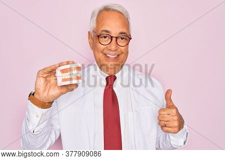 Middle age senior grey-haired dentist man holding prosthesis denture over pink background happy with big smile doing ok sign, thumb up with fingers, excellent sign