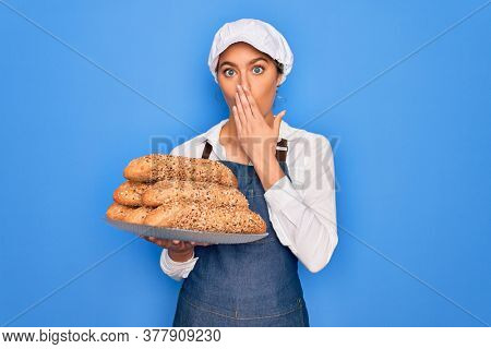 Young beautiful blonde baker woman with blue eyes holding tray with wholemeal bread cereal cover mouth with hand shocked with shame for mistake, expression of fear, scared in silence, secret concept