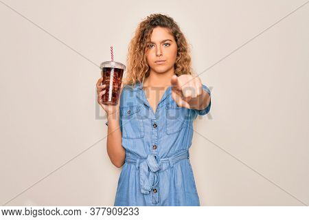 Beautiful blonde woman with blue eyes drinking cola beverage using straw to refreshment pointing with finger to the camera and to you, hand sign, positive and confident gesture from the front