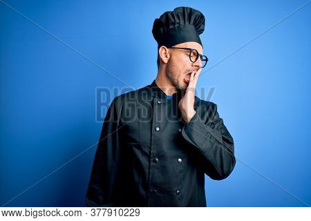 Young handsome chef man wearing cooker uniform and hat over isolated blue background bored yawning tired covering mouth with hand. Restless and sleepiness.