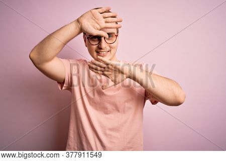 Young handsome redhead man wearing casual t-shirt standing over isolated pink background Smiling cheerful playing peek a boo with hands showing face. Surprised and exited