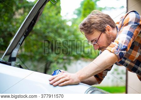 Man Checking And Refilling Fluid Levels In The Car, Side View. Vehicle Check-up.