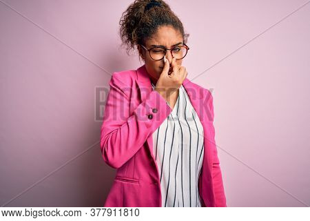Beautiful african american businesswoman wearing jacket and glasses over pink background smelling something stinky and disgusting, intolerable smell, holding breath with fingers on nose. Bad smell
