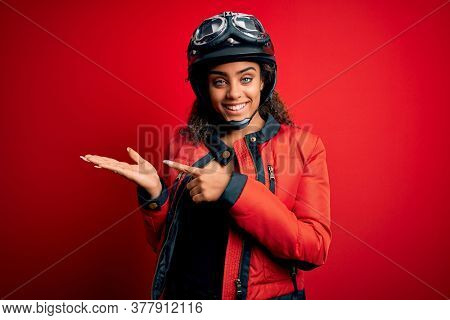 Young african american motorcyclist girl wearing moto helmet and glasses over red background amazed and smiling to the camera while presenting with hand and pointing with finger.