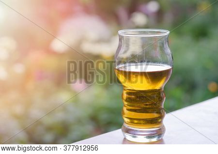 An Incomplete Glass Of Cold Beer On The Table In The Garden, Blurred Background