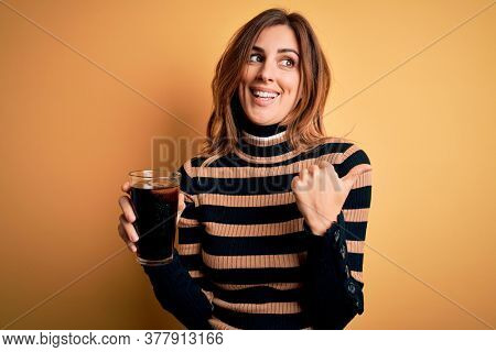 Young beautiful brunette woman drinking glass with cola refreshment using straw pointing and showing with thumb up to the side with happy face smiling