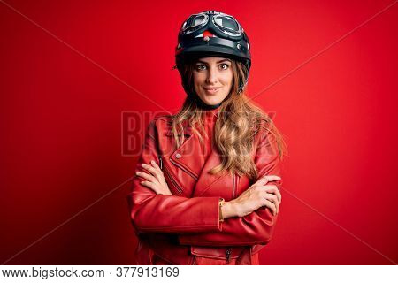 Young beautiful brunette motrocyclist woman wearing moto helmet over red background happy face smiling with crossed arms looking at the camera. Positive person.