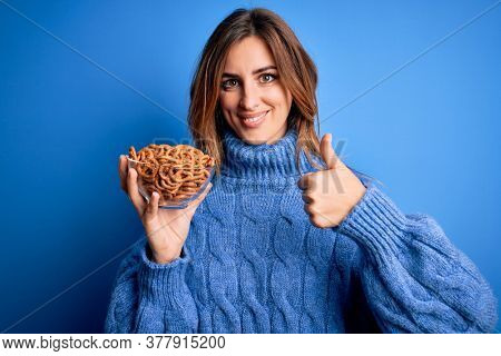 Young beautiful brunette woman holding bowl german baked pretzels over blue background happy with big smile doing ok sign, thumb up with fingers, excellent sign