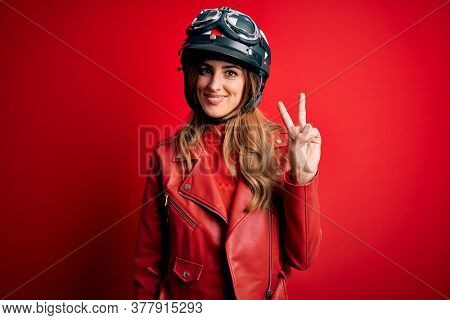 Young beautiful brunette motrocyclist woman wearing moto helmet over red background showing and pointing up with fingers number two while smiling confident and happy.