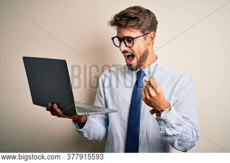 Young businessman wearing glasses working using laptop standing over white background screaming proud and celebrating victory and success very excited, cheering emotion